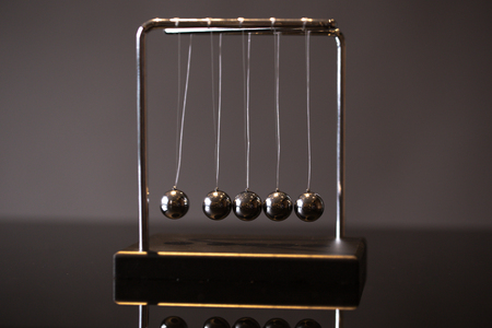 Closeup metal Newton cradle placed on gray background as representation of momentum concept 版權商用圖片