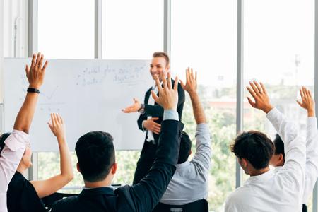 Veel deelnemers aan het bedrijfsleven steken hun hand op in een zakelijk seminar-conferentie-evenement in het bedrijfskantoor met een spreker vooraan