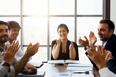 businesspersons clapping hands and applauding in business meeting conference. While female business executive sits in front - woman power in corporate Standard-Bild - 120424725