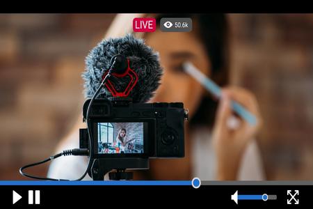 Giovane bella donna che registra video in streaming live per scopi commerciali di trucco e cosmetici online con interfaccia lettore video Archivio Fotografico