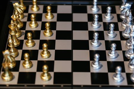 From above set of golden and silver chess pieces placed on board before match