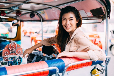 Young Asian female tourist woman exploring Bangkok, Thailand with local tuk tuk taxi and sightseeing the city