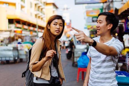 Jonge vrouwelijke toerist die om aanwijzingen en hulp vraagt van lokale mensen in Bangkok, Thailand