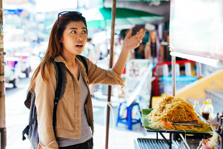 Young Asian woman tourist getting scammed and unhappy with overpriced street food in Thailand