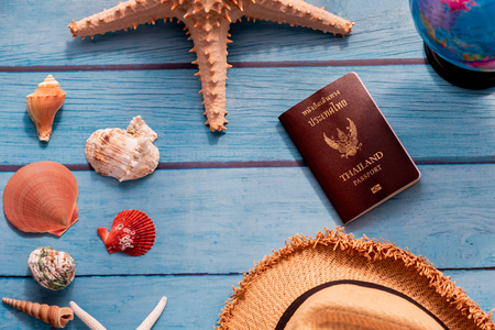 From above summer straw hat near world globe, sea stars with seashells, and Thai passport book on blue wooden background