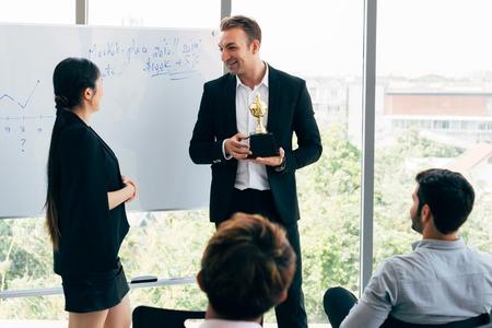 Allegro uomo d'affari caucasico che premia la dipendente di fronte ai colleghi durante il seminario nella sala riunioni dell'ufficio moderno