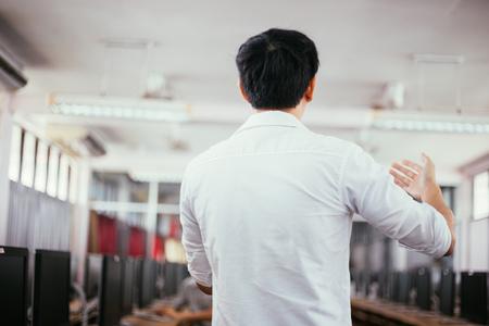 Rückansicht eines männlichen Geschäftsmannes, der in einem kleinen Raum in einer öffentlichen Veranstaltung spricht und einen Vortrag hält