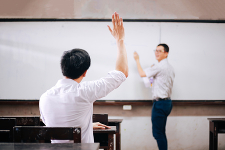 Young adult male student raising hands up in the air to ask questions from another male teacher