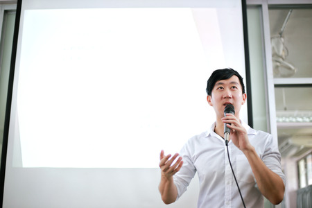 Portrait of young handsome Asian male speaker publicly speaking on stage to group of audience with white board behind