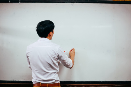 Businessman drawing and writing something on white board - with copy space