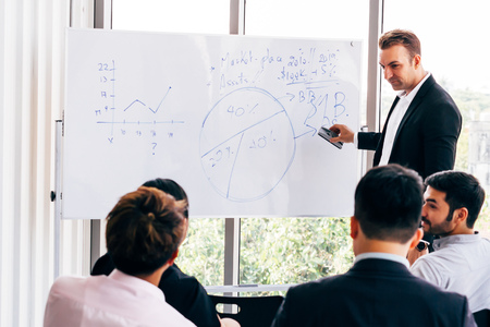 Adult Caucasian business coach wiping chart from whiteboard and listening to audience during conference in office Standard-Bild - 121074378