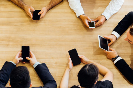 Crop from above of formal business men and women sitting in circle at table and using mobile phones in office