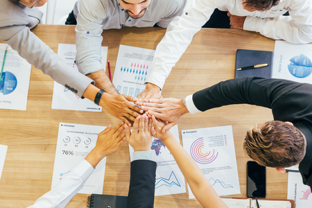 Ernten Sie Coworking-Geschäftsleute, die Hände über einem Holzschreibtisch mit Papierdokumenten stapeln