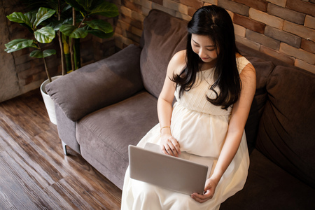 Top view of young beautiful Asian working pregnant woman using computer laptop and sitting on sofa at home - maternity leave from office work concept