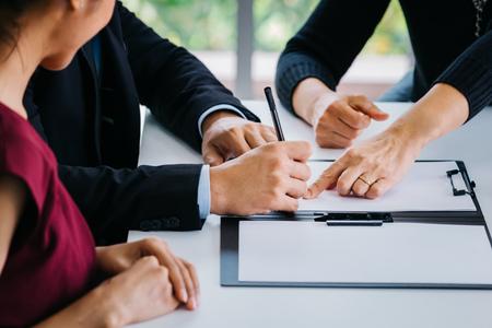 Primer plano de una pareja casada que firma documentos junto con otro testigo o agente: puede ser divorcio, ley, responsabilidad, acuerdo de prueba para el matrimonio Foto de archivo