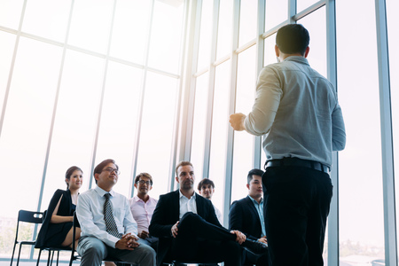 From below of businessman standing in front of colleagues in light sunny room and doing presentation