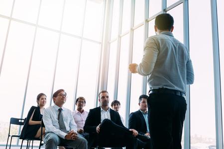 Van onderen van zakenman die voor collega's in lichte zonnige kamer staat en presentatie doet