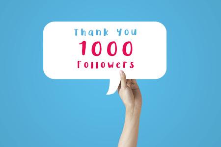 Close-up van een menselijke hand die omhoog staat en een zeepbel-toespraak houdt van 1000 volgers bedankt - mijlpaalbrief voor het vieren van sociale media