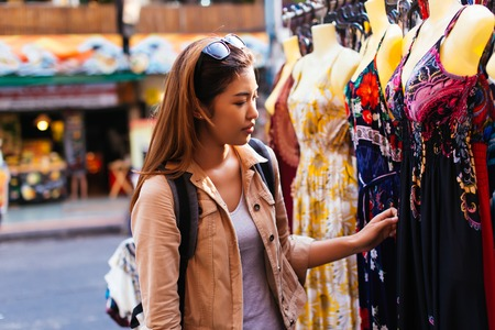 Young female Asian tourist woman shopping and choosing clothes on street market in Bangkok, Thailand