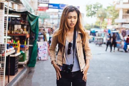 Giovane donna asiatica confusa che controlla le tasche dei jeans trovando la perdita di cose durante il viaggio in città