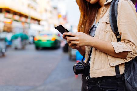 Giovane donna asiatica del turista femminile che utilizza un telefono cellulare a Bangkok, Tailandia. Chiamare un taxi o trovare informazioni durante il concetto di viaggio