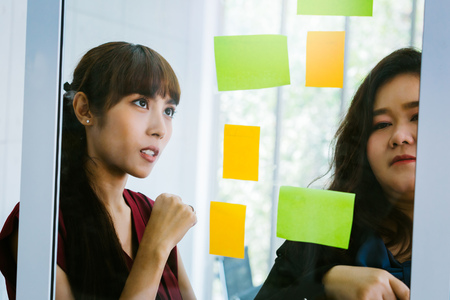 Close-up of serious and determined Asian business women looking at transparent glass board with sticky notes