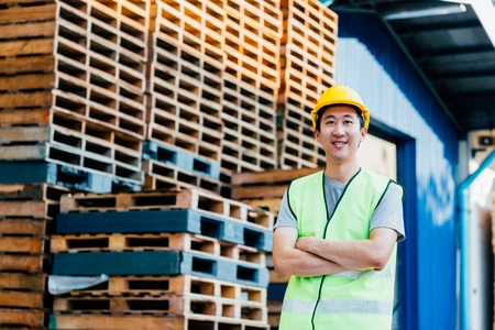 Smiling and happy Asian warehouse industrial adult worker equipped with hardhat and uniform posed with arms crossed in front of logistics distribution Banco de Imagens