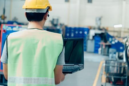 Asiatischer männlicher Wirtschaftsingenieur in Bauarbeiterhelm arbeitet mit Laptop in Sicherheitsjacke in der Schwerindustriefabrik. Verarbeitung von Kunststoffspritzgussindustrie