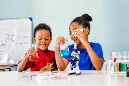 Dos niños mixtos afroamericanos pruebas de laboratorio de química y sosteniendo un frasco de tubo de vidrio con microscopio y una sonrisa en el aula de ciencias - concepto de aprendizaje divertido