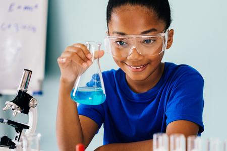 Experimento de laboratorio de química de prueba de niño afroamericano joven y agitar matraz de tubo de vidrio con microscopio y sonrisa - concepto de educación de ciencia y aprendizaje Foto de archivo