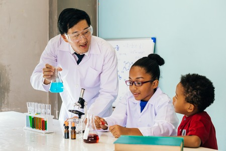 Young Asian scientist holding glass tube flask and teaching two African American mixed kids in chemistry lab experiment in science classroom