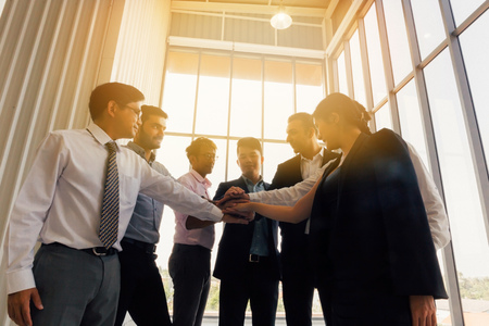 From below of multiethnic business men and women stacking hands together while standing in office in back lit