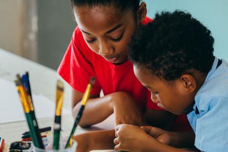 Primo piano di bambini afroamericani elementari che disegnano e dipingono in modo creativo con pennelli e pastelli - concetto di educazione creativa dei bambini