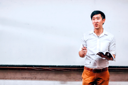 Young Asian man with textbook standing in spacious auditorium giving presentation