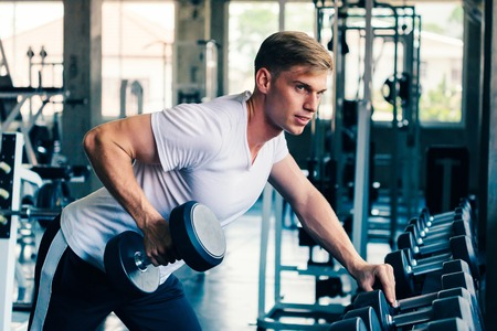 Young Caucasian man in white shirt at a gym, lifting heavy dumbbells with relaxation and looking away. Sport fitness and muscles concept