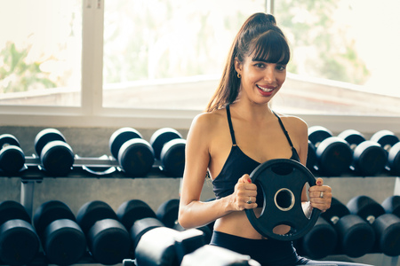 One happy smiling and healthy Caucasian woman in sportswear holding a weight plate with rack of dumbbells behind inside indoor gym, looking at camera. Stock Photo