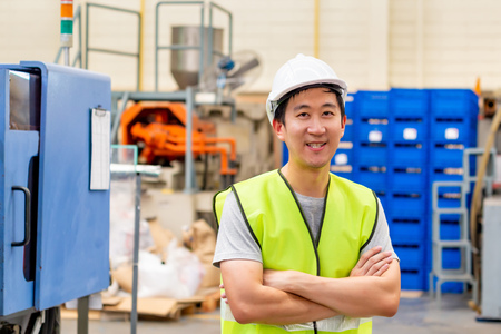 Front view of Asian factory worker with safety hard hat posed looking at camera with happy smile in industrial facilities at heavy industry manufacturing factory Imagens