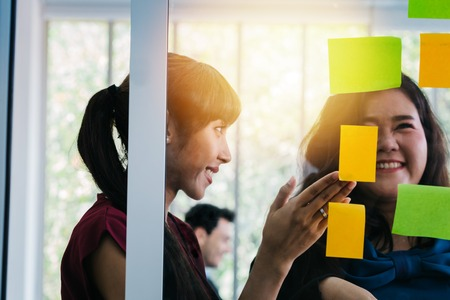 Female office managers smiling while looking at note stickers on glass wall in modern office