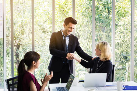 Business man and business woman shaking hands on meeting while female colleagues applauding in office