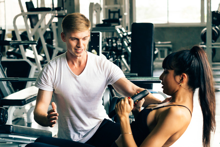 Young Caucasian male personal trainer in white shirt at a gym, helping and supporting female fitness client. She is doing situps. Sport fitness and muscles concept Banco de Imagens