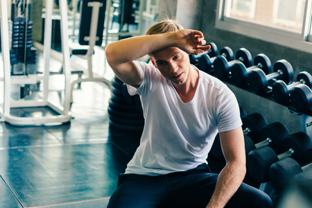 Young man wiping sweat off forehead with dumbbells and fitness equipment inside gym. He is tired and exhausted from weightlifting and weight training.