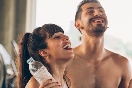 Two young happy smile Caucasian active man and woman refreshed from drinking water after gym caused by dehydration. They are in sportswear. Energy regained for fitness concept Banco de Imagens - 125116372