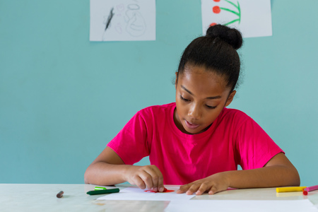 African American girl in bright T-shirt drawing with crayons while sitting at table against blue wall during art lesson at school Фото со стока