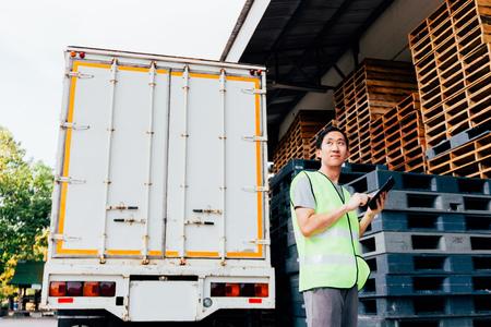 Junger asiatischer männlicher Logistiklagervertriebsunternehmer, der Tablette verwendet. Er ist umgeben von vielen Paletten und Lastwagen in Versandfracht.