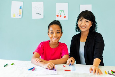 Cheerful Asian woman smiling and looking at camera while teaching African American girl to draw with crayons at table in art school