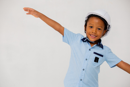 African American preschool boy wearing hard hat helmet outstretching arms and spread wings in white isolated background