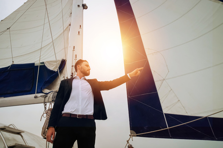 Young confident businessman pointing finger forward on sailing yacht with ship mast in the background - leadership and visionary business concept Stock Photo