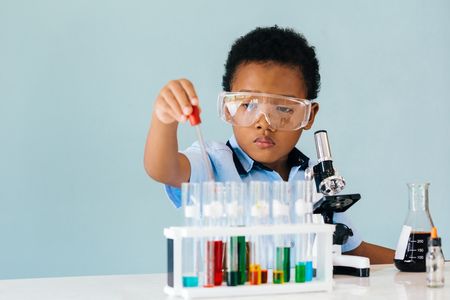 Serious African American boy in protective goggles using pipette while trying to learn how to mix colorful chemicals in laboratory Imagens