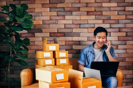 Young Asian male business entrepreneur use computer laptop and phone with boxes to deliver customers from orders - Online business and ecommerce