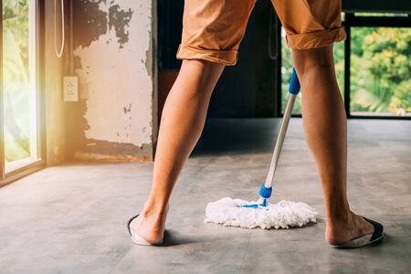 Low section of human legs and feet wearing slippers using mopping tool to clean up inside the living room at home - cleanliness and housekeeping concept